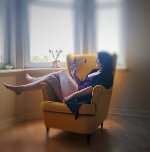 Hannah in a yellow winged armchair wearing a purple chemise and black robe.