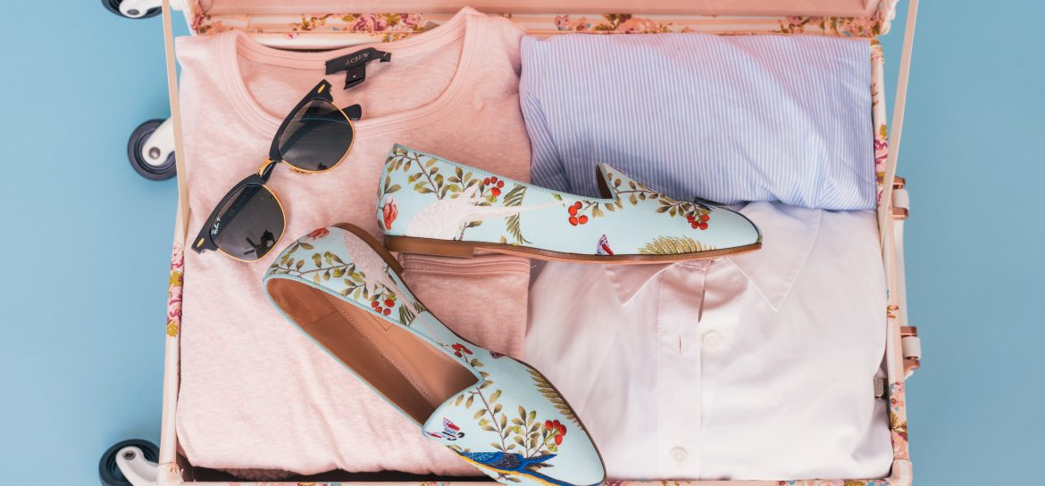 pink suitcase with pink and baby blue clothes shoes and sunglasses