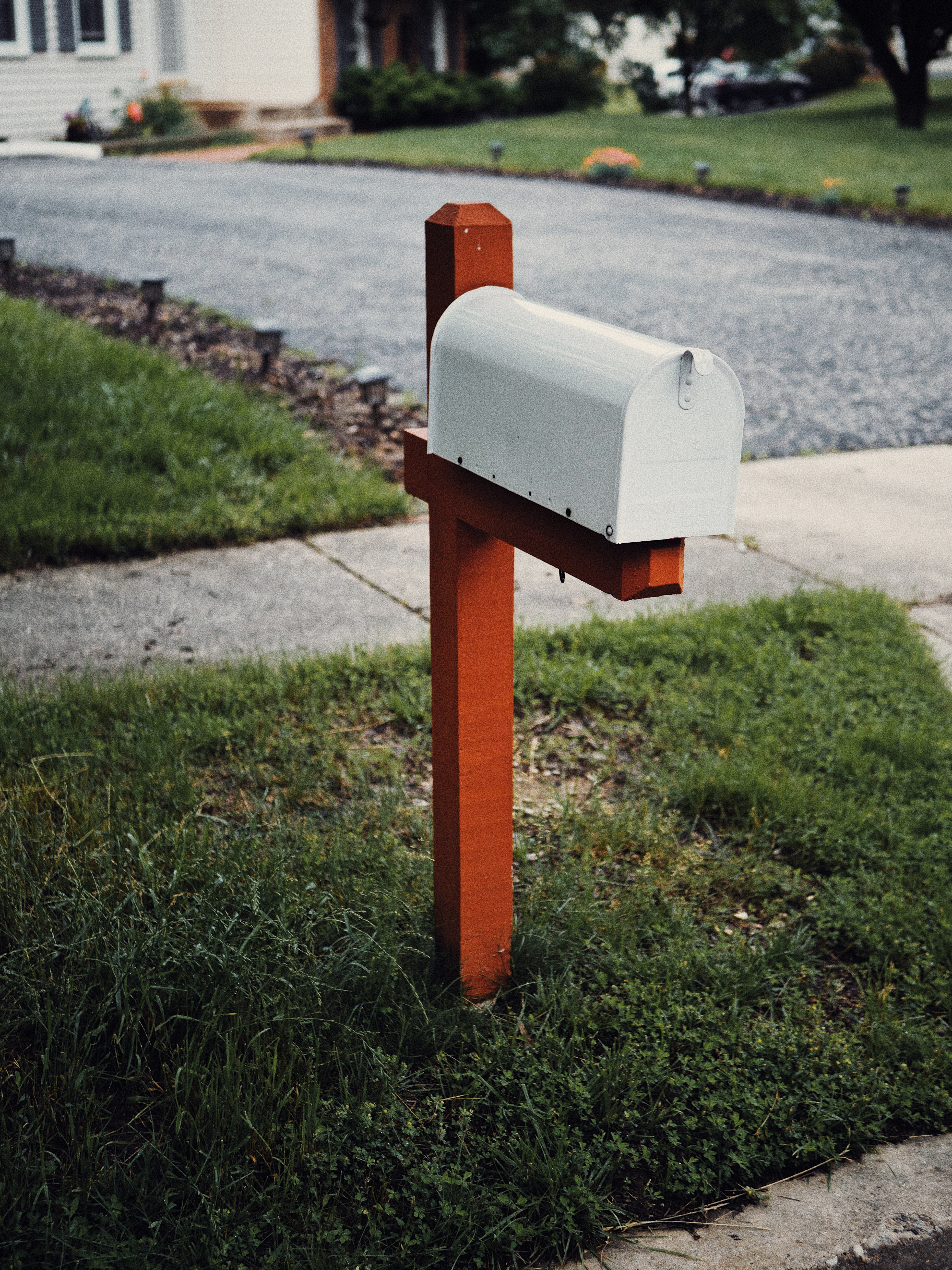 White mailbox in front of a side walk and the side of a house with a green lawn