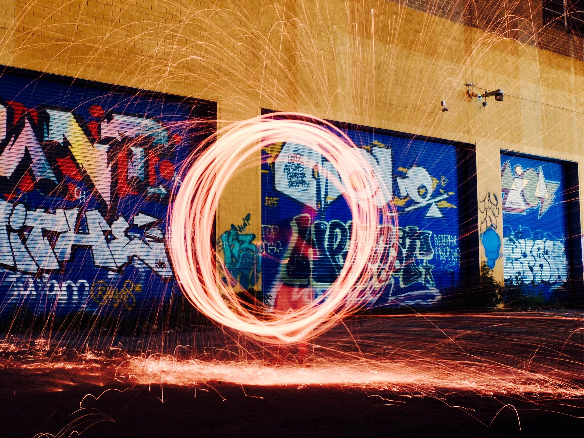 O made out of sparks in front of graffiti