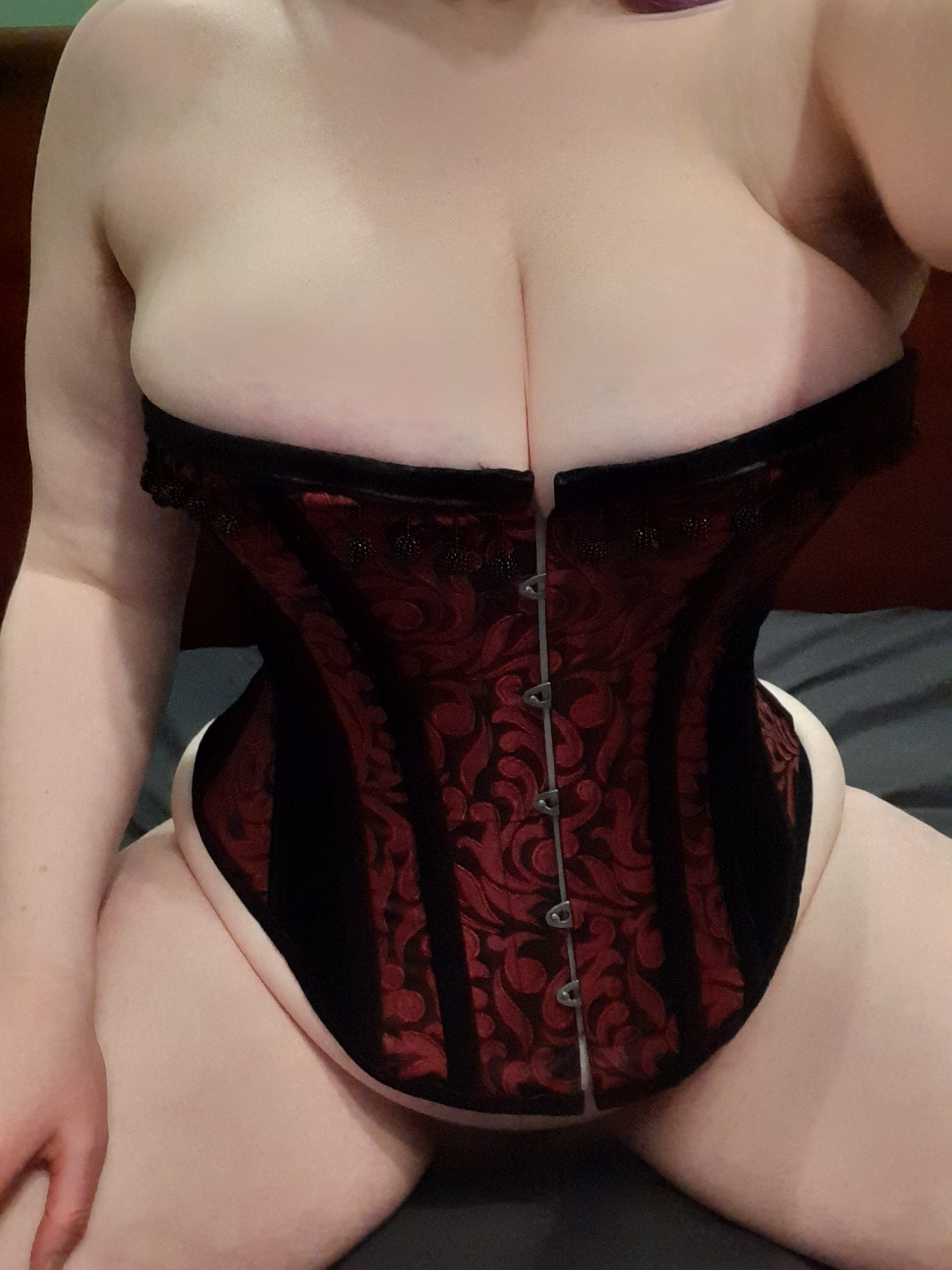 Woman posing on a bed in a corset