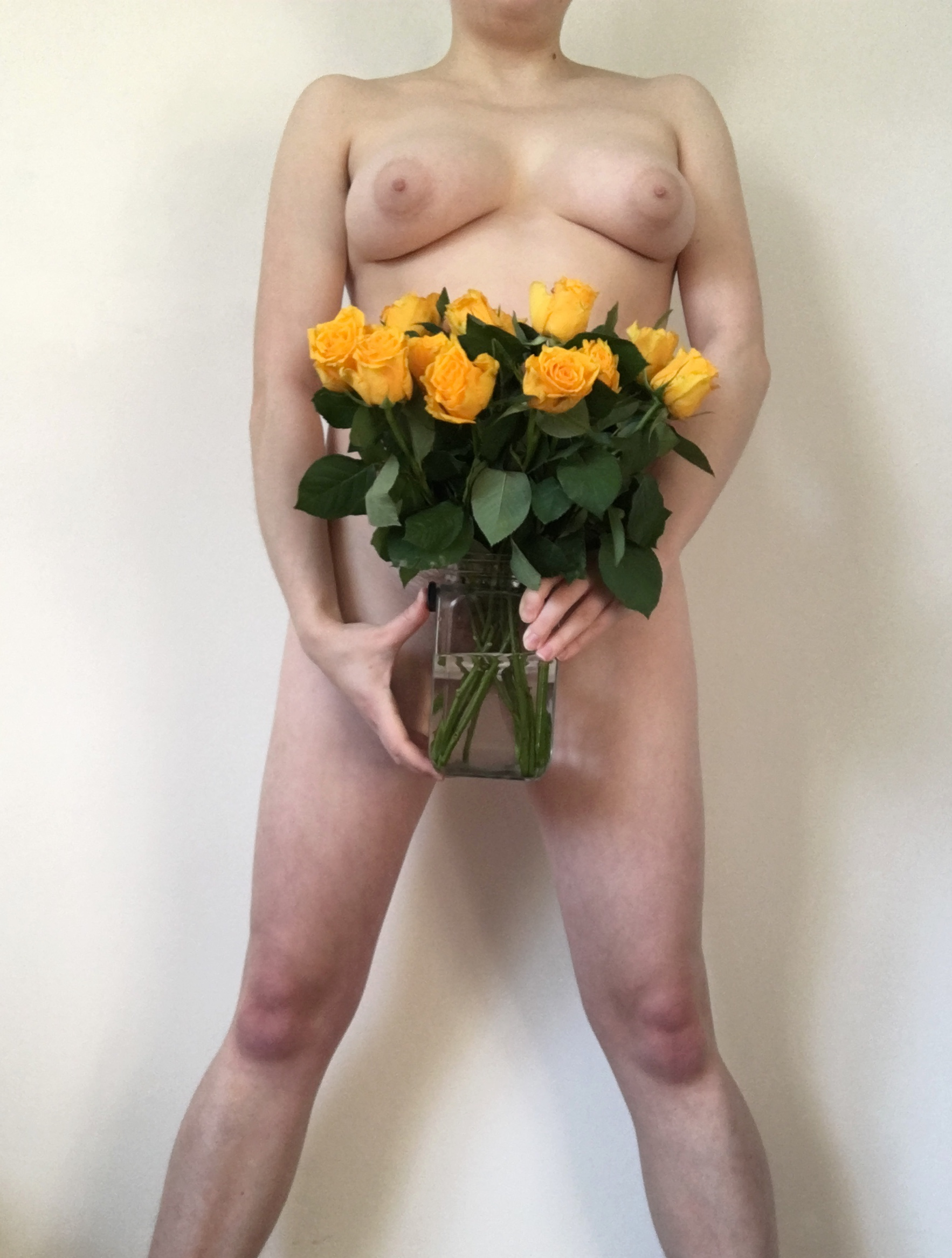 A naked trans guy holds a vase of yellow roses in front of his crotch. Photo.