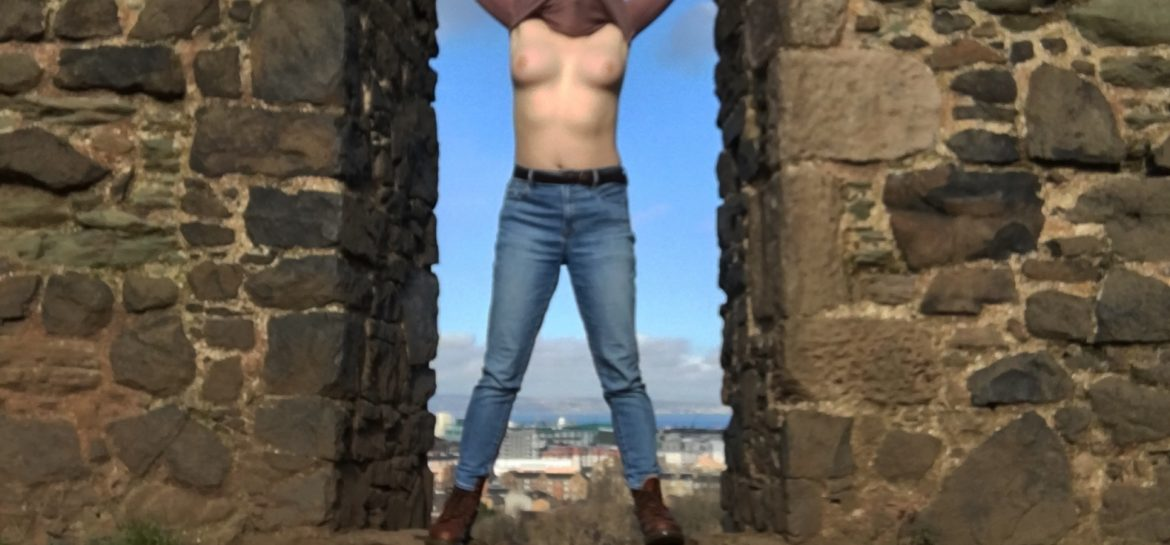 A trans guy stands in a stone doorway, wearing jeans but with his top pulled over his head to expose his tits. Photo.