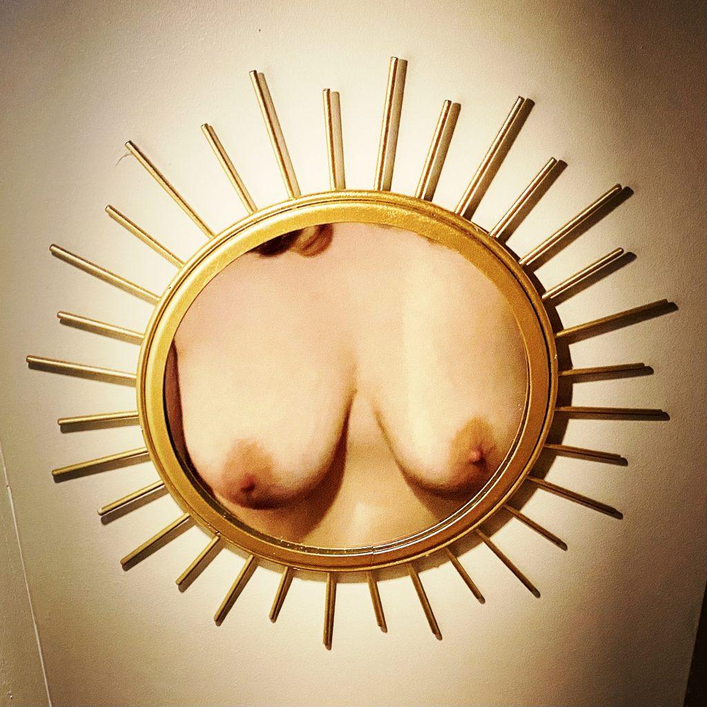 A photo of my tits, taken in a golden sunburst mirror